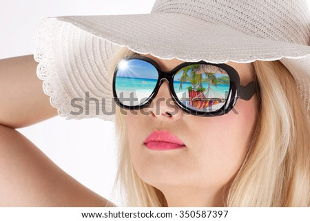 fine portrait of young cute woman with summer hat and sun glasses looking at the beach in a sunny day - stock photo