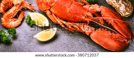 Fine selection of crustacean for dinner. Steamed lobster with lemon on dark background - stock photo