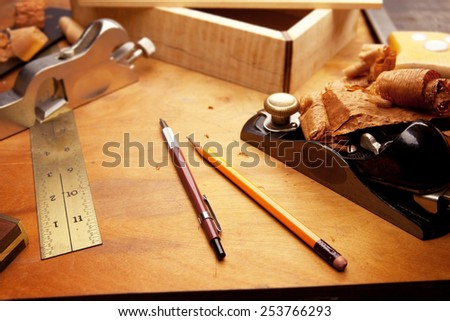 Fine wood working. Saw, hand plane, pencils and a wooden shavings on a work desk under incandescent light.Focus is on forehand side of two pens.  - stock photo