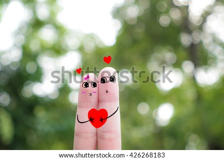 Finger art of a Happy couple. A man and a woman hug with pink hearts in the eyes .funny-finger-people -couple-smiling - stock photo