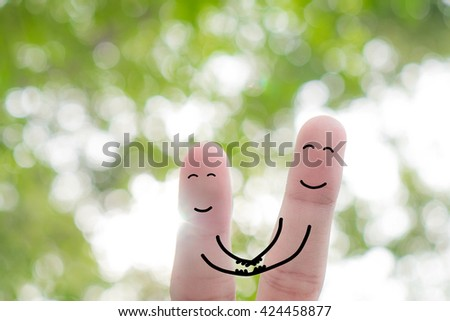 Finger art of a Happy couple. A man and a woman hug with pink hearts in the eyes. The concept of love at first sight. - stock photo