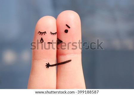 Finger art of displeased couple. Woman cries, man reassures her. He kisses and hugs her. - stock photo