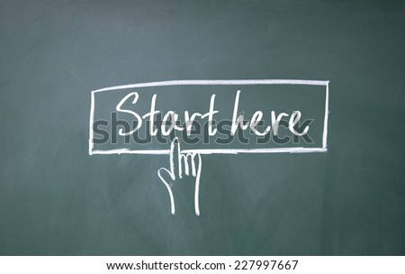 finger click start here symbol on blackboard - stock photo