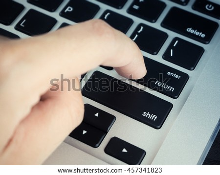 "Finger clicking ""Enter and Return button"" on laptop keyboard - stock photo"