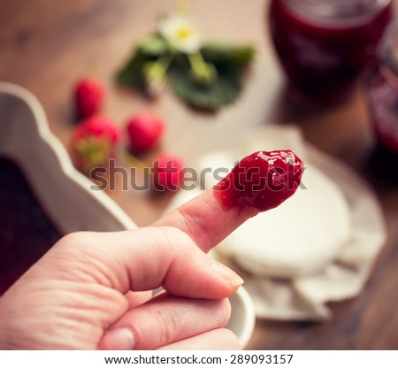 Finger dipped in strawberry jam. Homemade strawberry jam (marmalade) concept.  - stock photo