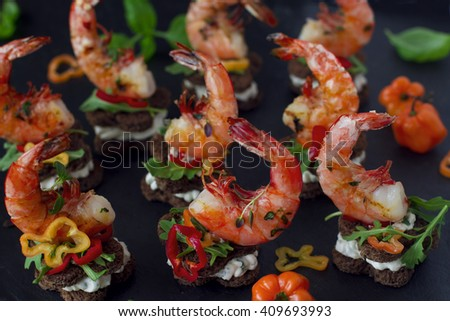 Finger food: rye mini toasts with Philadelphia cheese, grilled king shrimps, habanero pepper and herbs - stock photo
