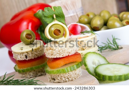 finger foods made of bread, peppers, cucumber cheese and olives on wooden table - stock photo