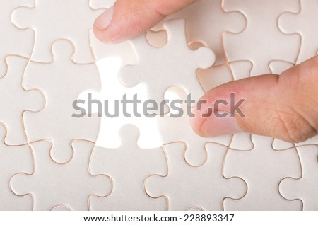 finger holding missing piece in jigsaw puzzle concept of finding business solution for problem missing link - stock photo
