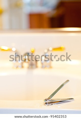Finger nail clippings on bathroom sink with gold faucets or taps - stock photo