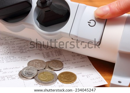 Finger of woman turns off electrical extension, electrical plugs connected to electrical power strip, electricity bill with coins, concept for energy saving - stock photo