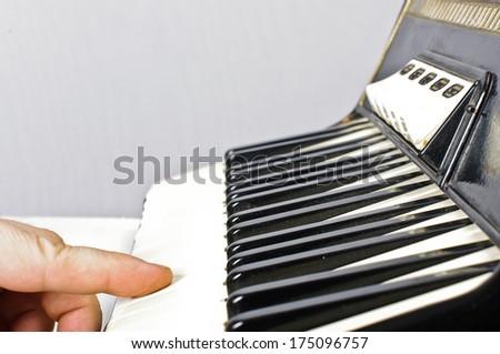 Finger on acordion keyboard - stock photo