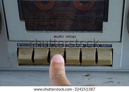 finger press on play button of old tape cassette - stock photo