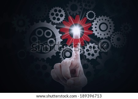 Finger pressing a cog gear symbolizing business control - stock photo