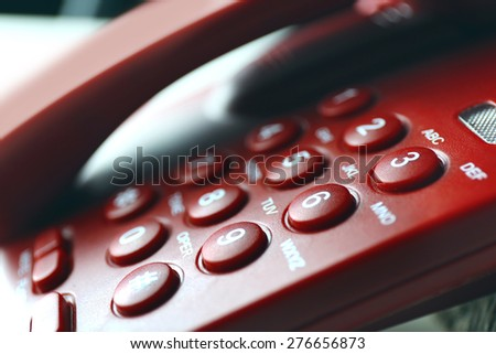 Finger pressing number button on telephone to make a call, close up - stock photo