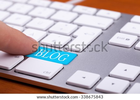 Finger pressing on blog button on keyboard. Online writing and succes - stock photo