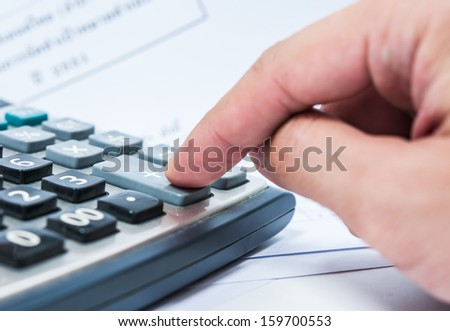 Finger pressing on plus sign on calculator - stock photo