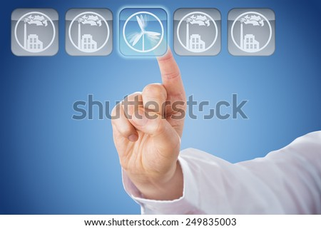 Finger pushing a button with a translucent wind energy icon. Lighting up in blue, this key is in the center of a line-up of five. The other four grey keys do show smoking factories. Blue background. - stock photo