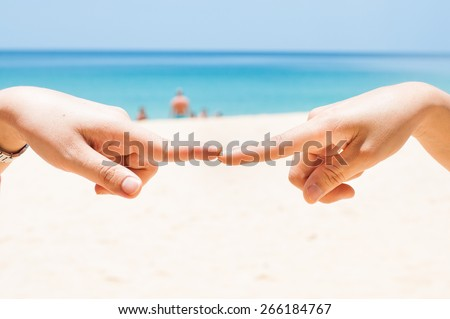 Finger touch with two hand on the beach.Show the ties.Connection or contact symbol. - stock photo