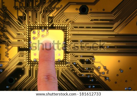 finger touching and make the glow line on PCB - stock photo