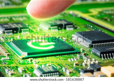 finger touching  glow start symbol on  microprocessor  - stock photo