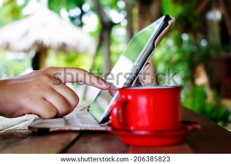 Finger touching on tablet with red cup on table in garden - stock photo