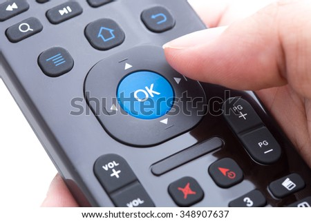 Finger will push ok button on remote control over white background - stock photo