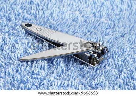 fingernail clippers on blue, terry towel - stock photo