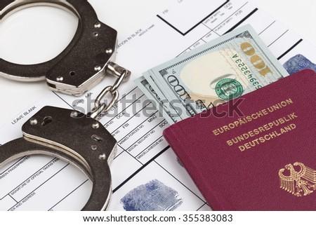 Fingerprint card with german travel passport and handcuffs - stock photo