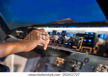 fingers controls the switch control panel in a plane cockpit - stock photo