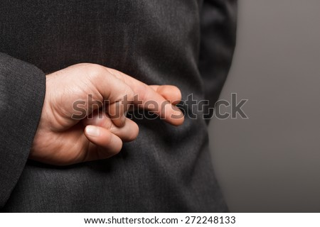 Fingers crossed behind back. - stock photo