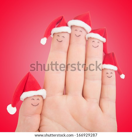 Fingers faces in Santa hats against red background. Happy family celebrating concept for Christmas day. - stock photo