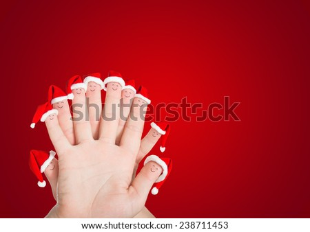 Fingers faces in Santa hats against red background. Happy friends or family celebrating holiday concept for Christmas or New Years day. - stock photo