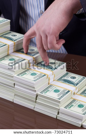 fingers of a businessman walking on a bundle of money - stock photo