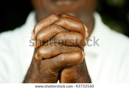 fingers of afro man clasped in front of his body - stock photo