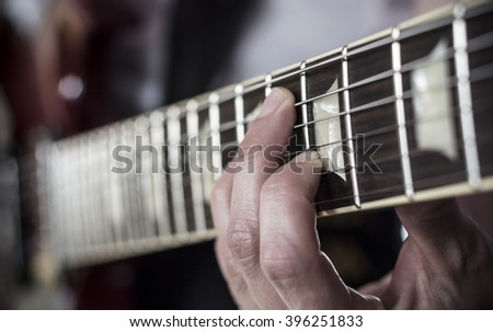 Fingers over guitar - stock photo
