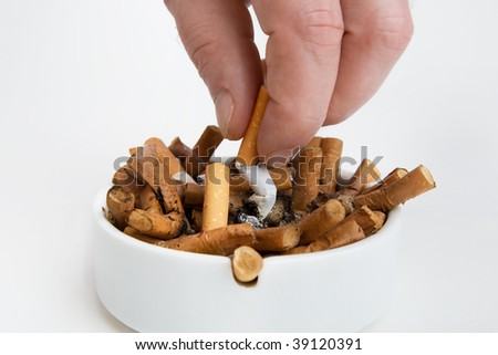 Fingers with cigarette butt in an ashtray - stock photo