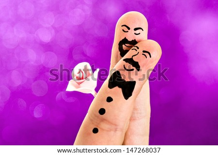 Fingers with sweet faces painted featuring a gay wedding between a man with a moustache and a bowtie and a guy with a beard an a rose - stock photo