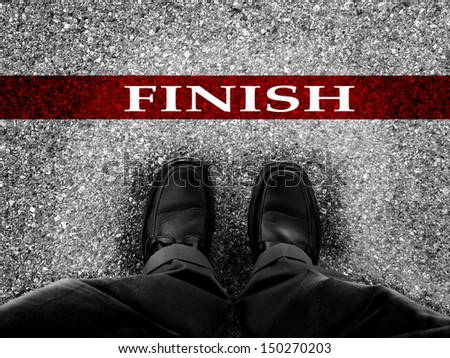 Finish line with businessman wearing dress shoes as metaphor for finishing work as a winner     - stock photo