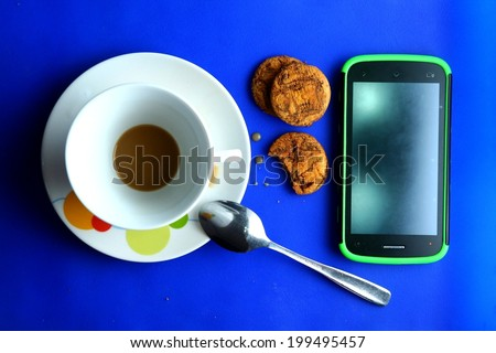 Finished Coffee in a ceramic cup, cookies and a cellphone Photo of a finished or drank coffee in a ceramic cup and saucer, a teaspoon and three cookies and a cellphone - stock photo