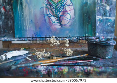 Finished colorful painting on dirty easel with brushes, paint tube and flower, Artist workspace picture - stock photo
