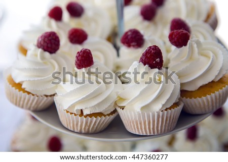 finished cupcakes with white cream and raspberries - stock photo