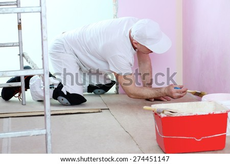 Finisher in white clothes with a brush in hand painted walls in pink room near the floor - stock photo