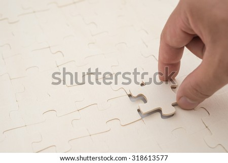 finishing the last piece of a jigsaw puzzle game on white - stock photo