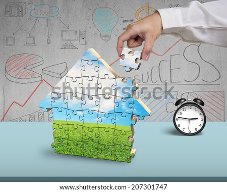 Finishing to assemble house shape puzzles in office - stock photo