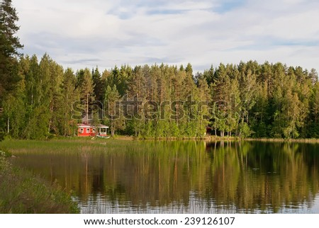 Finnish house on the shore of lake forest. - stock photo