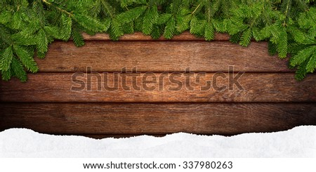 fir branches and snow on wooden background - stock photo