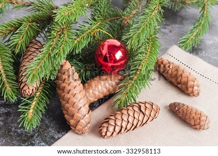 fir cones, Christmas ball and Green fir branches on black background, closeup, horizontal - stock photo
