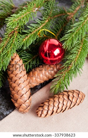 fir cones, Christmas ball and Green fir branches on black background, closeup, vertical, top view - stock photo