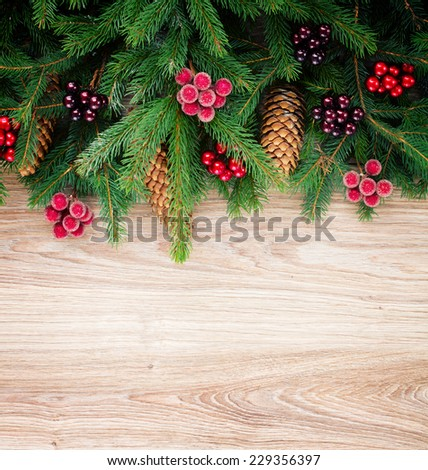 fir tree border with cones and berries on wooden background with copy space, retro toned - stock photo