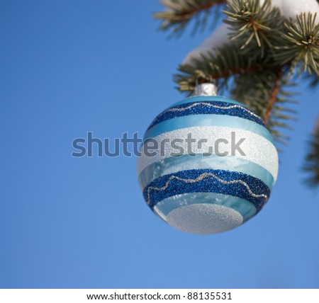 Fir tree branch decorated with christmas ball on blue sky background - stock photo